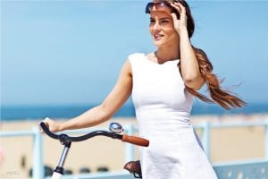 Model in White Dress Standing Next to Bike